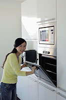 Young woman opening oven door and smiling - Alex Mares-Manton