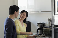 Couple talking together in kitchen - Alex Mares-Manton