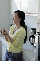 Woman leaning against kitchen counter holding coffee mug - Alex Mares-Manton