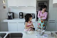 Mother watching her daughter cook in the kitchen - Alex Mares-Manton