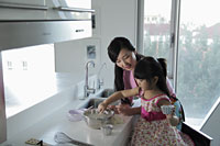 Mother teaching daughter how to cook - Alex Mares-Manton