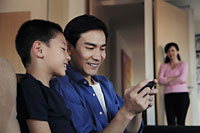 Father playing game with son on phone - Alex Mares-Manton