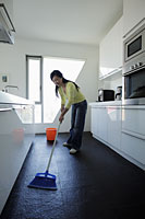 Woman sweeping her kitchen floor - Alex Mares-Manton
