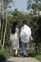 Rear view of young couple walking down a path - Alex Mares-Manton