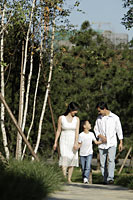 Young family holding hands walking down path - Alex Mares-Manton