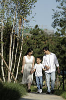 Young family walking down a path and holding hands - Alex Mares-Manton
