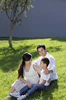 Young family sitting on the grass smiling - Alex Mares-Manton