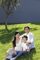 Young family sitting on grass smiling - Alex Mares-Manton