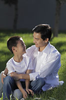 Father and son sitting on grass smiling at eachother - Alex Mares-Manton