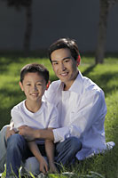 Father and son sitting on grass together smiling - Alex Mares-Manton