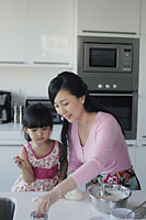 Mother teaching her daughter how to cook - Alex Mares-Manton