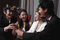 Two couples celebrating at a party, toasting each other - Alex Mares-Manton