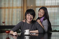Young couple at cafe smiling - Alex Mares-Manton