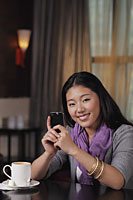 Young woman sitting in restaurant holding phone - Alex Mares-Manton