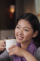 Head shot of young woman holding coffee cup - Alex Mares-Manton