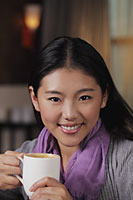 Head shot of young woman holding coffee cup and smiling - Alex Mares-Manton