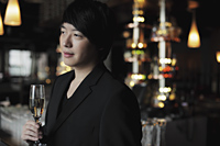 Profile of young man holding a glass of champagne. - Alex Mares-Manton