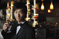 Young man in a tuxedo holding a glass of champagne - Alex Mares-Manton