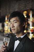 Head shot of man in a tuxedo holding a glass of champagne - Alex Mares-Manton