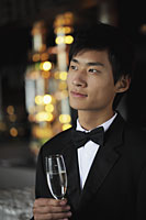 Head shot of young man wearing a tuxedo and holding a glass of champagne - Alex Mares-Manton