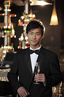 Young man dressed in a tuxedo holding a champagne glass at night - Alex Mares-Manton