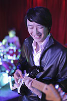 Young man playing guitar in a club - Alex Mares-Manton