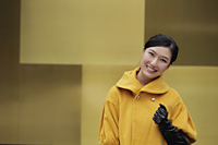 Young woman in yellow coat smiling - Alex Mares-Manton