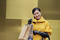 Young woman in  yellow coat holding shopping bags - Alex Mares-Manton