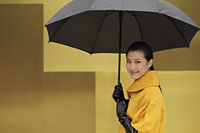 Young woman smiling at camera holding an umbrella - Alex Mares-Manton