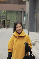 Young woman wearing yellow coat and gloves shopping outdoors - Alex Mares-Manton