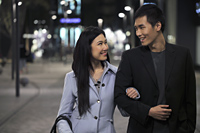 Young couple wearing coats walking on the street at night - Alex Mares-Manton