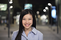 Head shot of young woman smiling on the street at night - Alex Mares-Manton