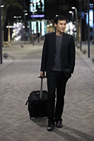 Young man walking down a street pulling a suitcase - Alex Mares-Manton