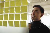 man looking at sticky notes and smiling - Alex Mares-Manton