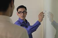 Man explaining something while writing on white board - Alex Mares-Manton