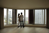 Rear view of young couple looking out large windows of condo - Alex Mares-Manton