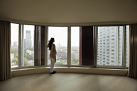 Young woman looking out large windows of condo - Alex Mares-Manton
