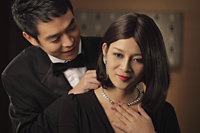 Young man putting a diamond necklace onto a woman - Alex Mares-Manton
