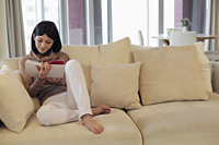 Young woman sitting on sofa reading a book in living room - Alex Mares-Manton