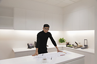 Young man dressed in black standing in modern office - Alex Mares-Manton
