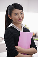 Young woman holding pink folder and smiling - Alex Mares-Manton