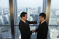 Two men shaking hands in front of window with a view of the city of Beijing - Alex Mares-Manton