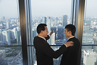 Two men talking in front of window with a view of the city of Beijing - Alex Mares-Manton