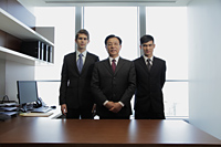 Three business men standing behind a desk - Alex Mares-Manton