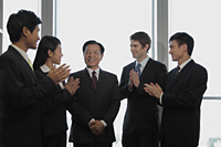 Small group of business people smiling and clapping - Alex Mares-Manton