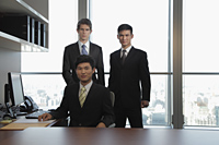 Three businessmen standing together in an office - Alex Mares-Manton