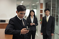 Three businesspeople standing in office, one texting on a phone - Alex Mares-Manton