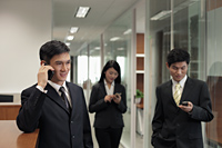 Three businesspeople using their phones in the office - Alex Mares-Manton