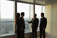 Businesspeople talking in front of a window in an office - Alex Mares-Manton