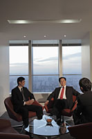 Three businessmen talking in an office - Alex Mares-Manton